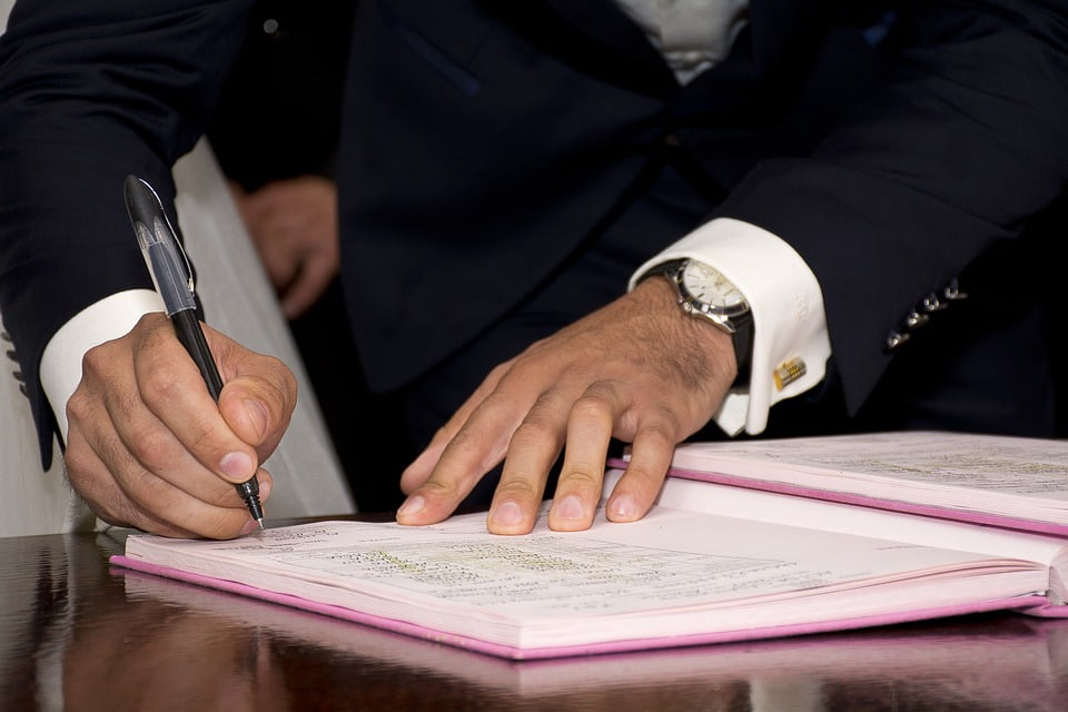 close up of man signing a document