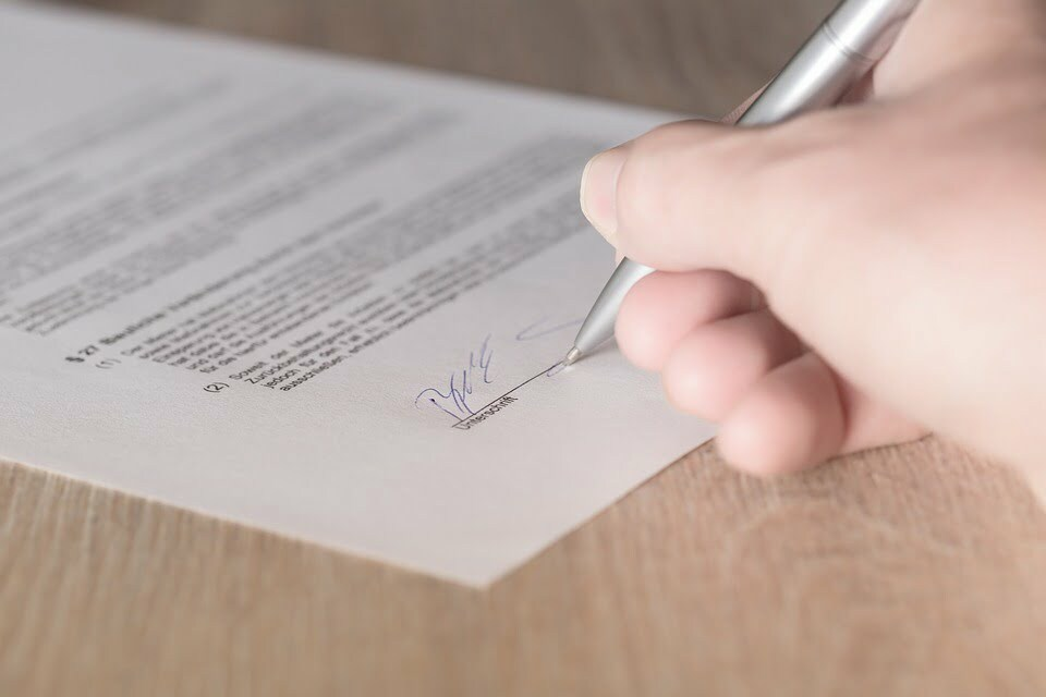 close up of man signing a document 2