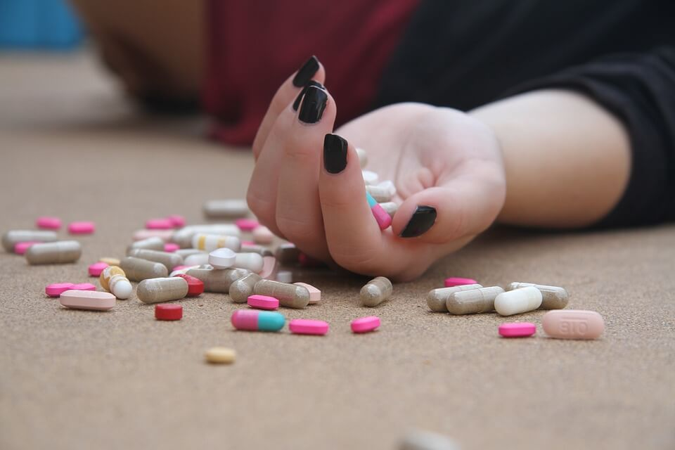 girls hand with pills suggesting suicide attempt