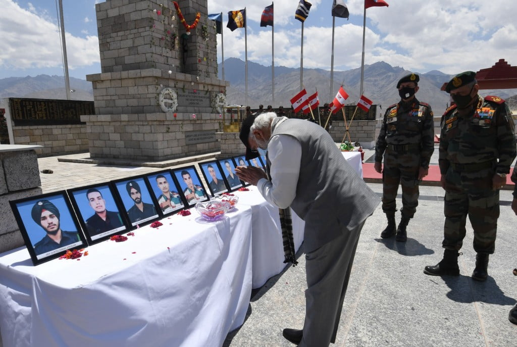 PM bowing down in front of slain soldiers photo