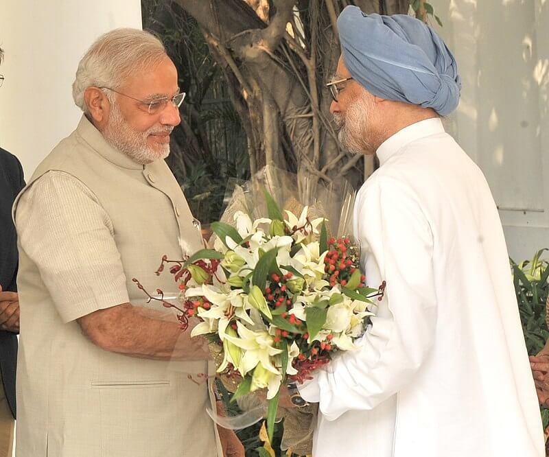 Manmohan singh presenting a flower bouquet to Modi